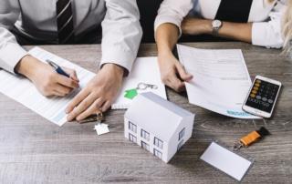Réunions de juristes pour établir un projet de SCI en train de signer des documents avec les clés des biens immobiliers et une maquette de maison