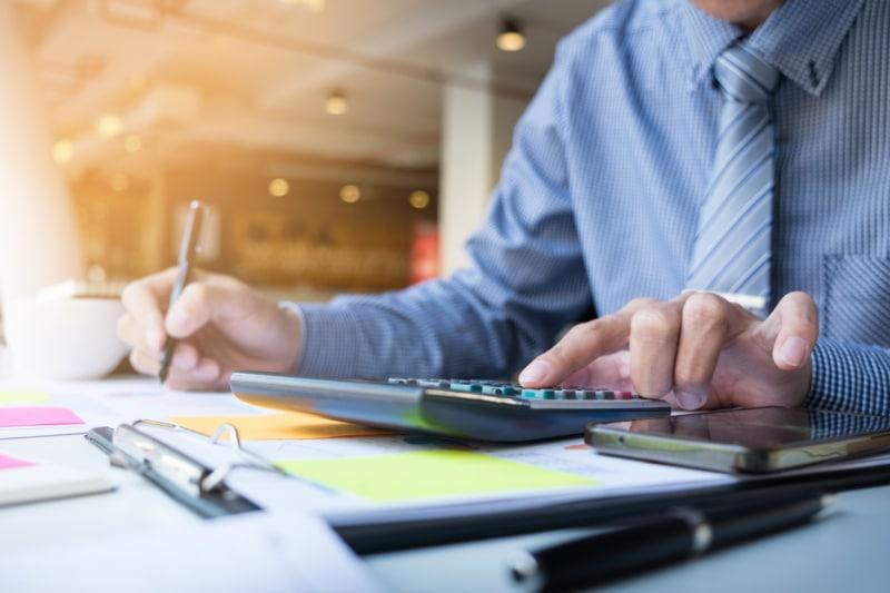 Homme d'affaire financier qui calcule son budget avec factures et une calculatrice