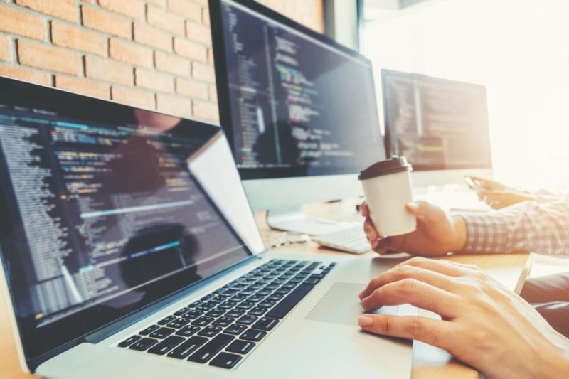 Programmeur en développement de sites Web e travaillant dans un bureau avec son macbook pro et son café