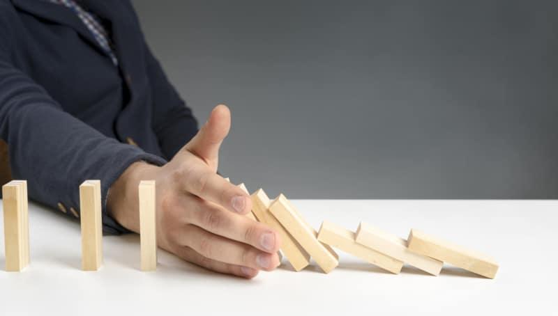 Homme en costume qui retient des dominos jaune de tomber avec sa main