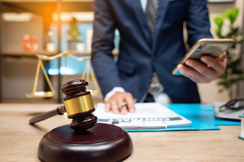Homme d'affaire en train de rédiger un business plan juridique avec son téléphone à la main et le marteau du barreau devant