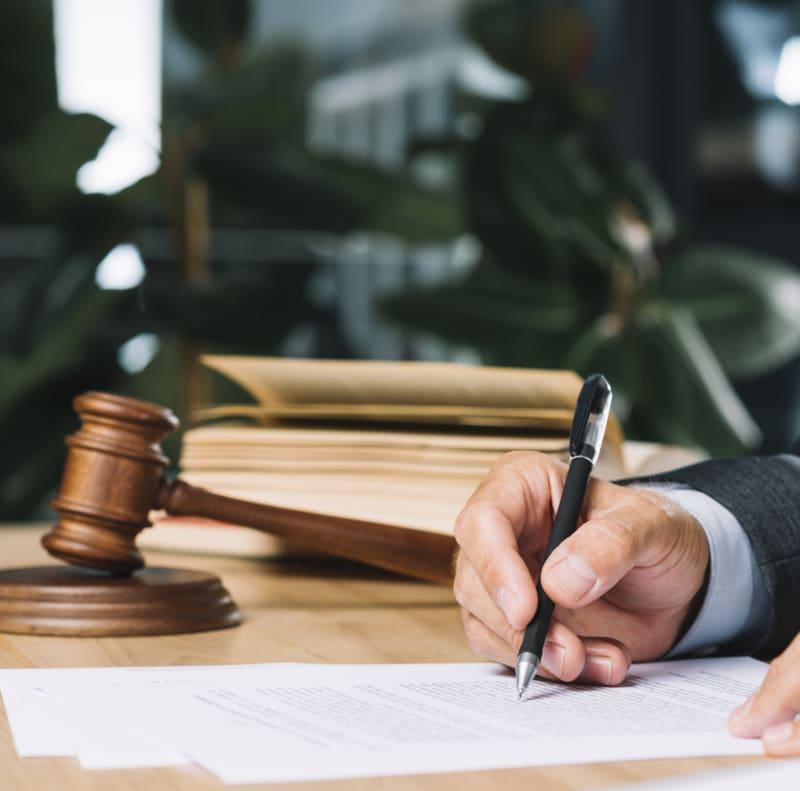 Juriste en train de signer un document avec un stylo bille avec le code civil et le marteau de juge