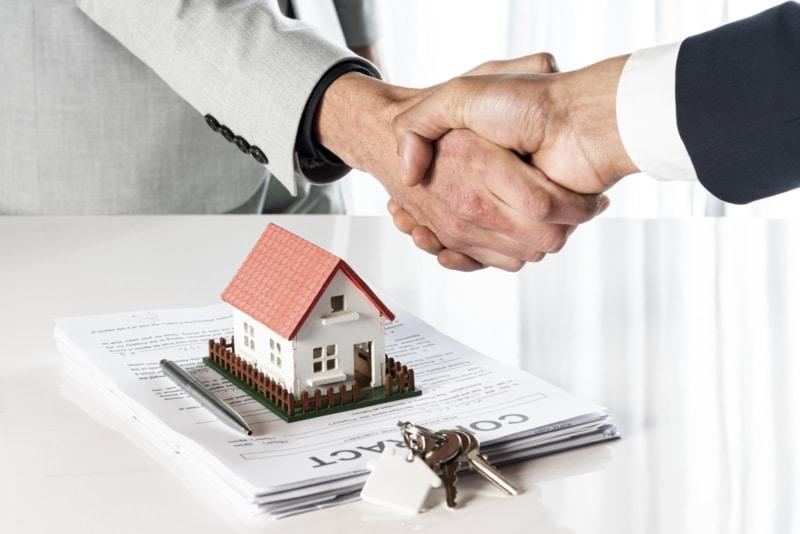 Poignée de main avec un contrat immobilier et des clés
