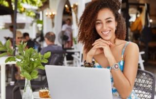 Femme souriant et cherchant sur son ordinateur comment devenir autoentrepreneur