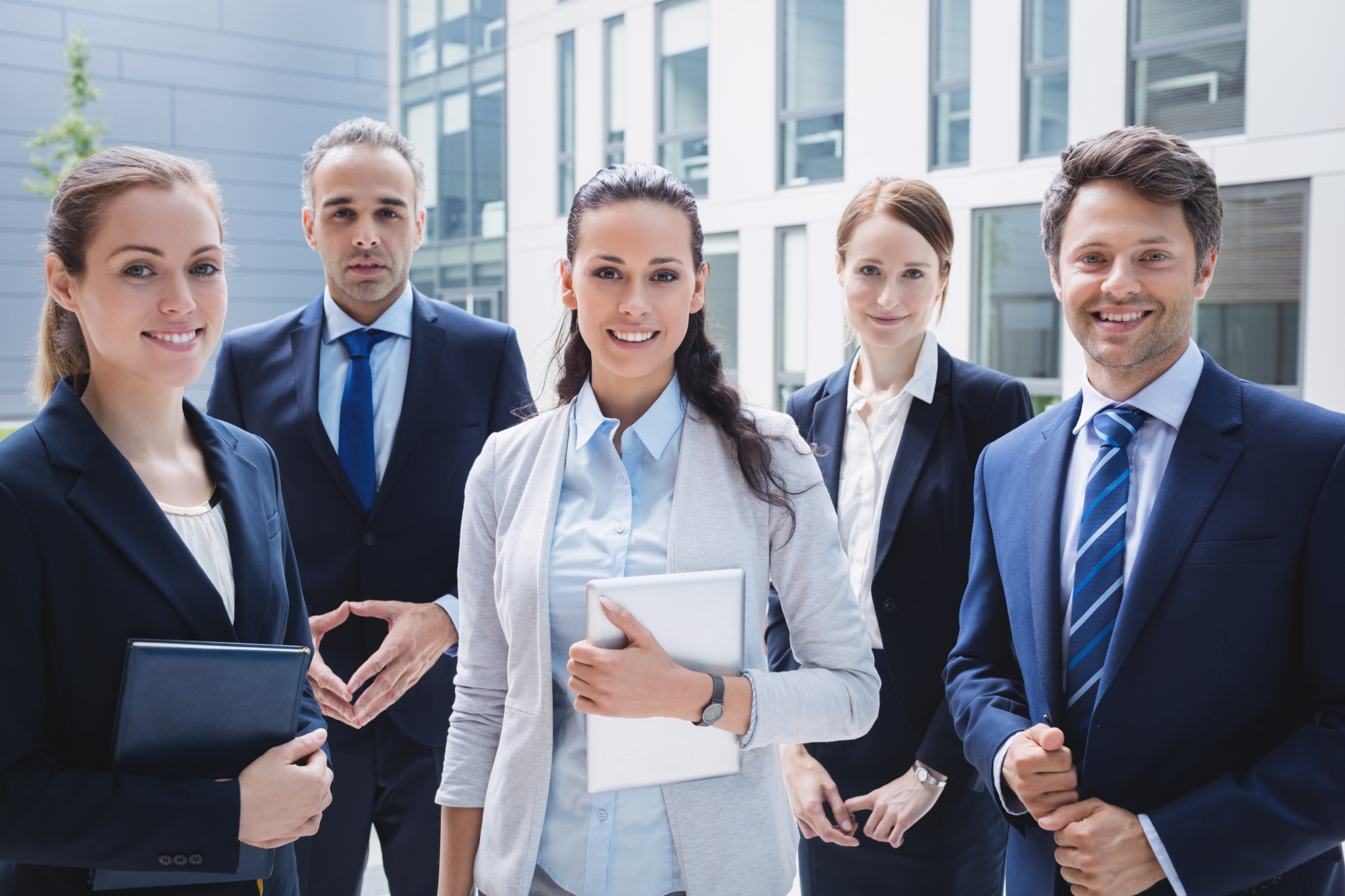 Hommes et femmes d'affaires se tenant devant un batiment d'affaire