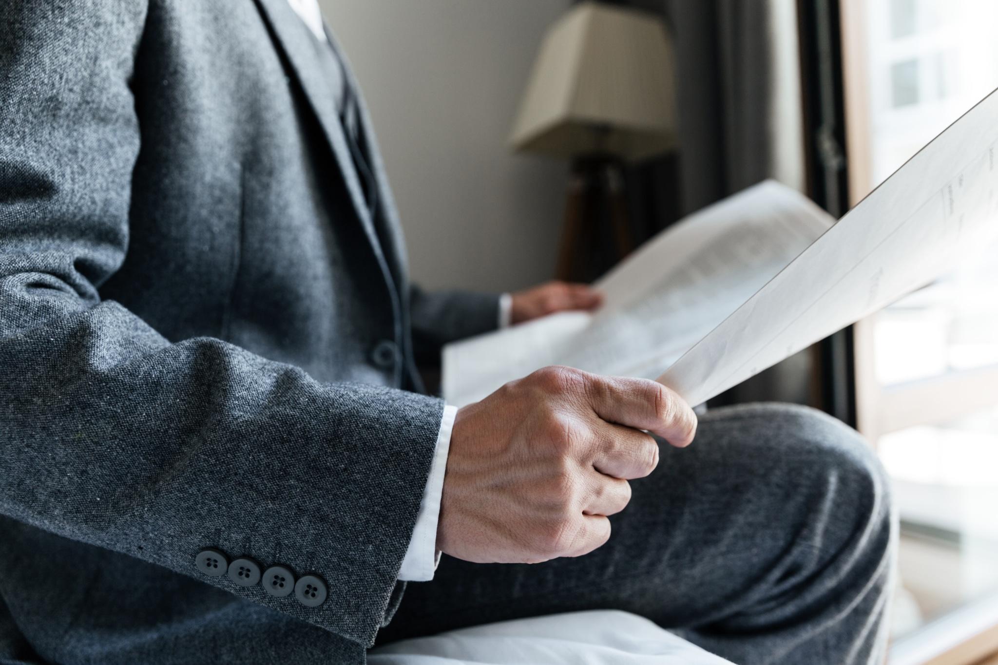 Homme en costume lisant son journal
